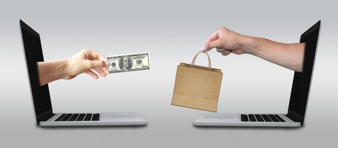 Imagen de dos manos atravesando dos pantallas de ordenador realizando una compra-venta.