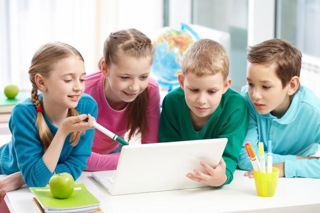 Grupo de cuatro ni�os estudiando juntos con un ordenador port�til.