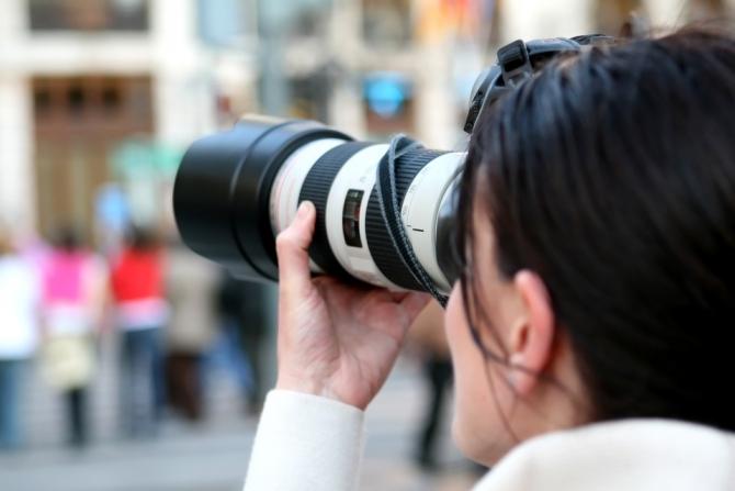 Imagen de una mujer con su c�mara de fotos realizando una fotograf�a.